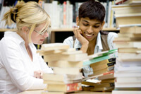 Two students studying in a library surrounded by books