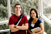 Male student in red t-shirt standing with female student in blue t-shirt hold books. Both are smiling