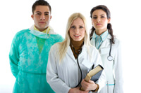 Three medical professionals, the two women on the right are wearing coats and stethoscopes, the man on the left is wearing a scrubs