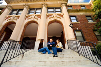 Three graduate students sitting on the steps in front of the archway to a tan university building