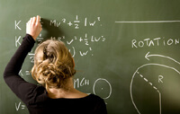 Teacher in a long black sleeve shirt with a blonde bun writing equations on a green chalkboard