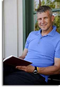Man in a blue polo holding a book, looking at the camera, and smiling