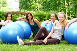Four women sitting on grass. Each has a blue yoga ball