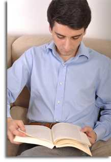 Man in a light blue button up shirt sitting and reading