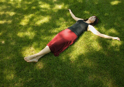 Woman in a black tan-top and long maroon skirt lying on the grass, with arms outstretched and eyes closed