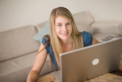 Girl sitting behind a coffee table in front of a tan couch, smiling at her laptop