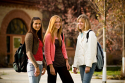 Three female students in jackets standing and smiling outside their university