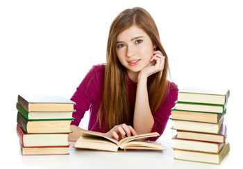 Smiling girl sitting in front of an open book in between two stacks of books